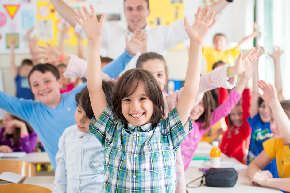 Young people waving hands in a classroom environment