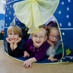 Three children play in a tent